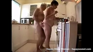 Old couple having fin in the kitchen